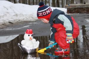 Тимур (2 года) отправляет снеговика в плавание по весенним ручейкам и лужам.